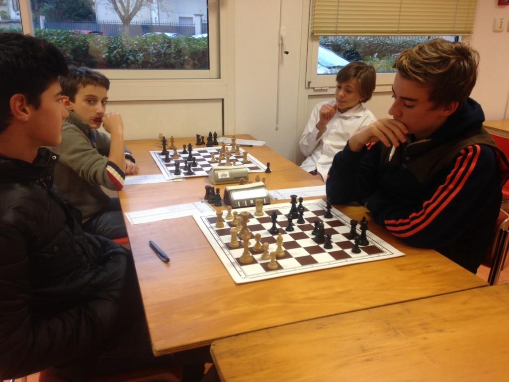 Le moment décisif sur les échiquiers minimes : pendant que Gaspard, au second plan, savoure sa position gagnante, Valentin cherche en vain comment contrer le Ca4! de son adversaire.